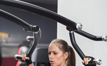 lady working out on shoulder press machine in gym